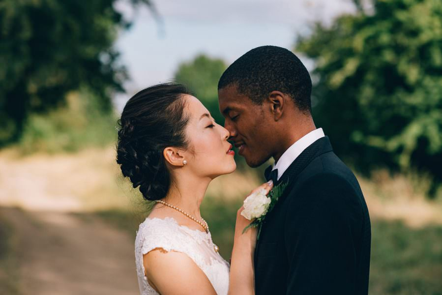bride reaches up to kiss her groom at an oxford wedding