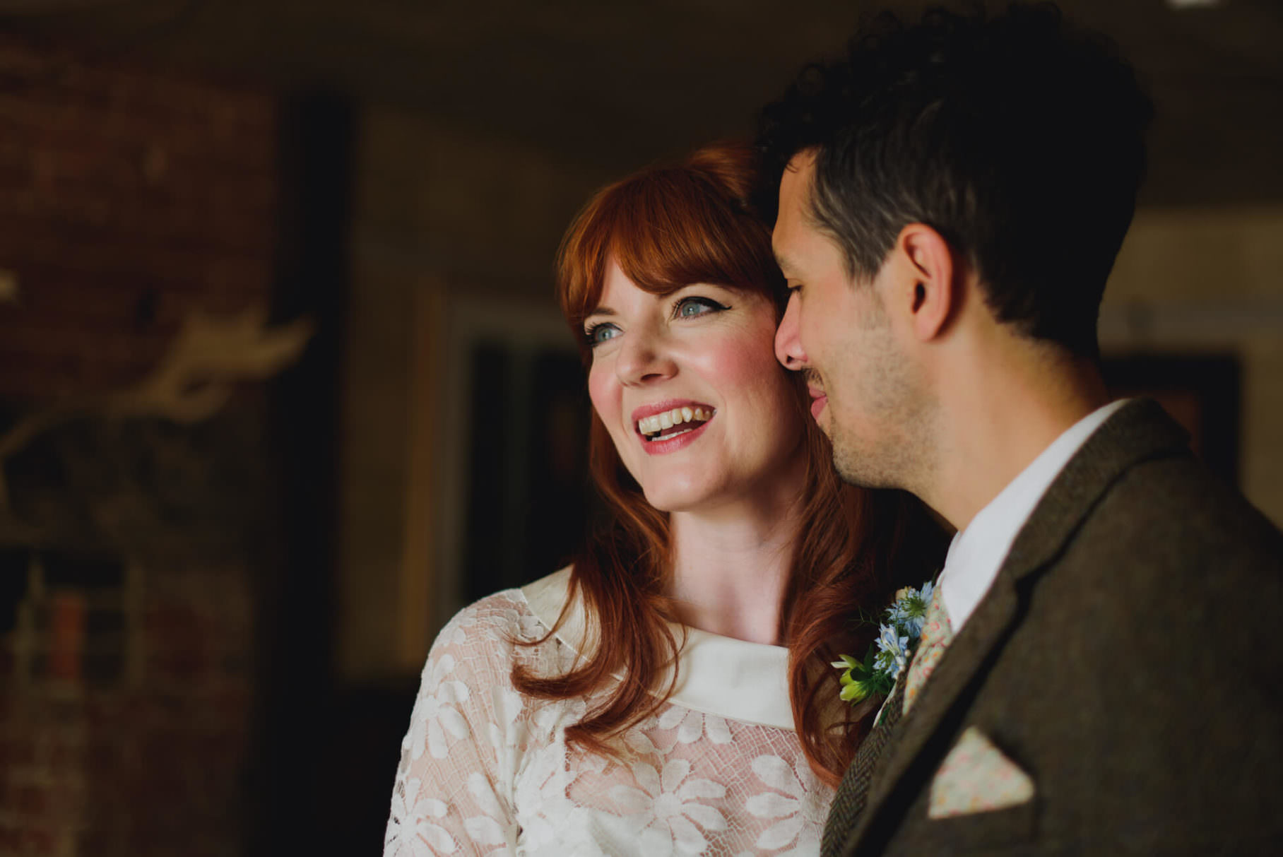 bride and groom smiling in the window light at The Bell in ticehurst