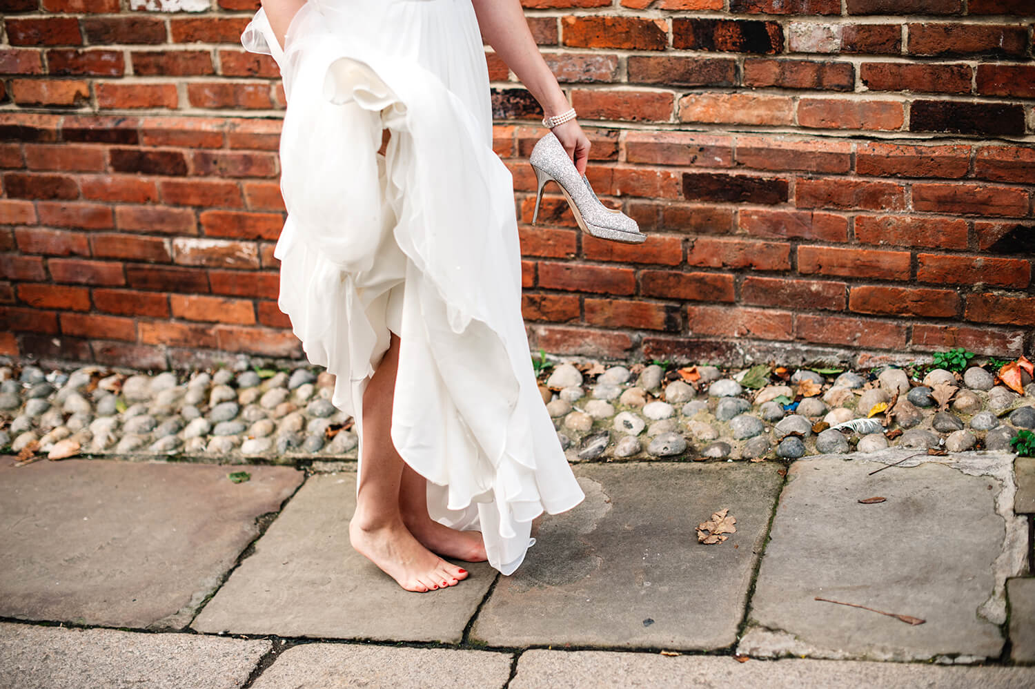 close up of Bride's feet walking barefoot with shoes in her hands