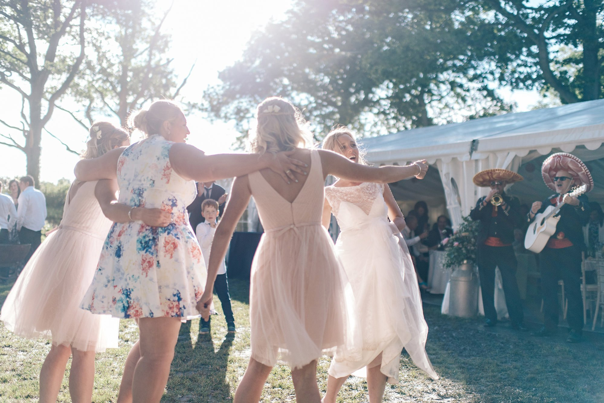 bride and her bridesmaids dancing in the mud