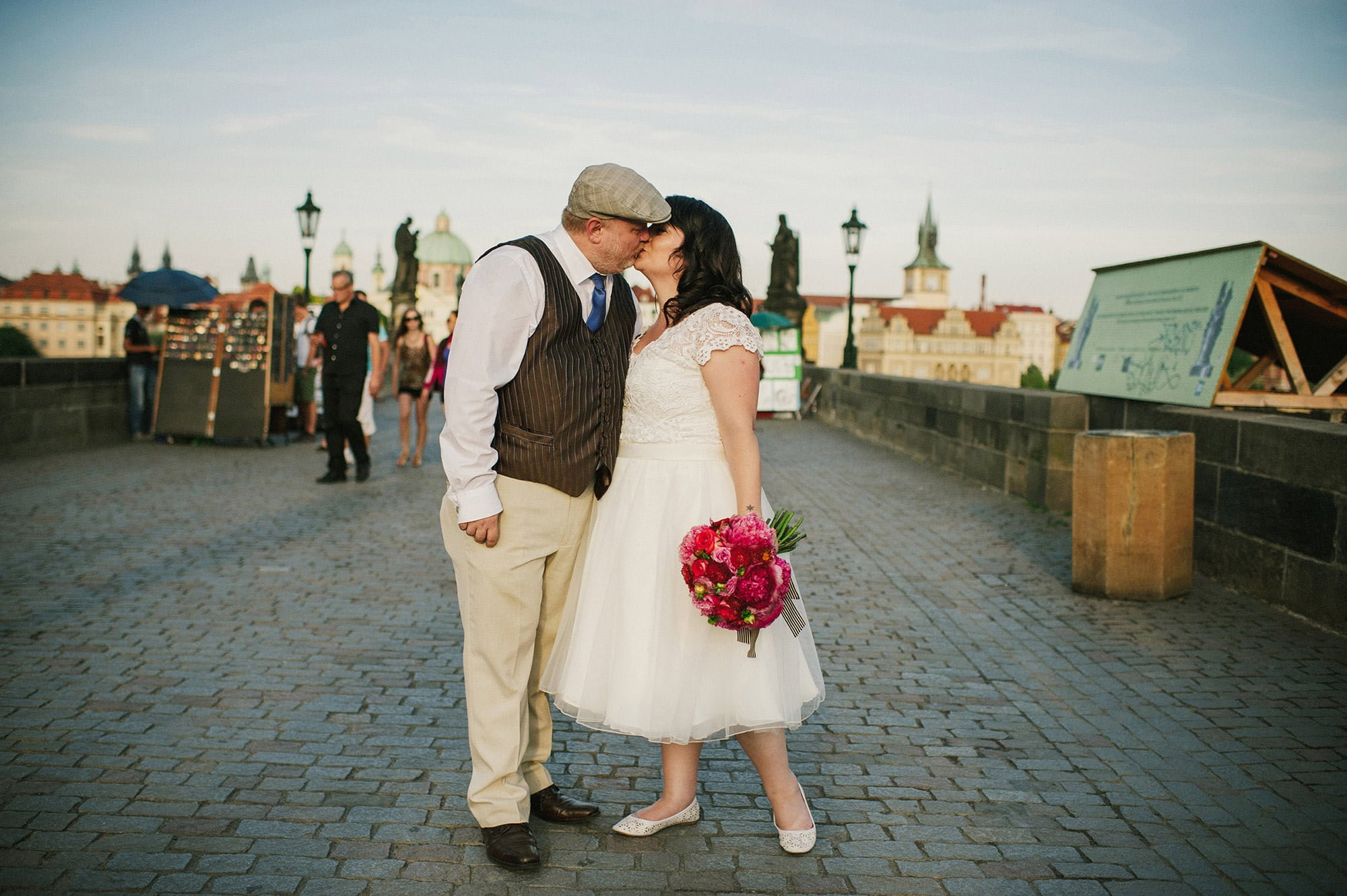 bride and groom kissing on Charles Bridge Prague