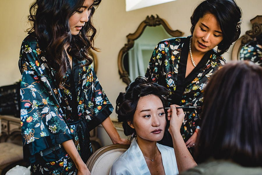 bride getting ready surrounded by her bridesmaids
