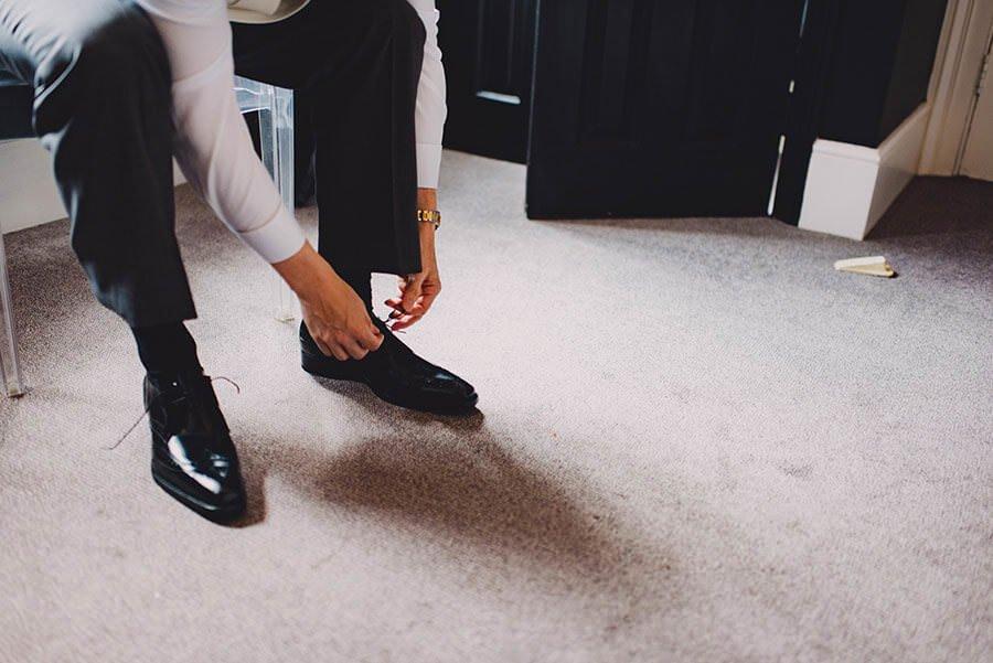 groom tying shoelaces