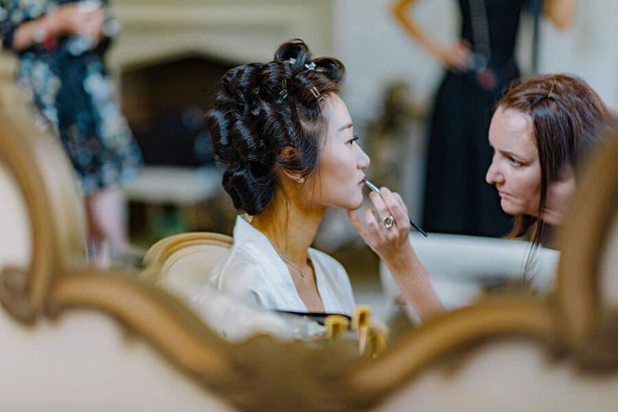 bride reflected in mirror having her makeup done at nonsuch mansion