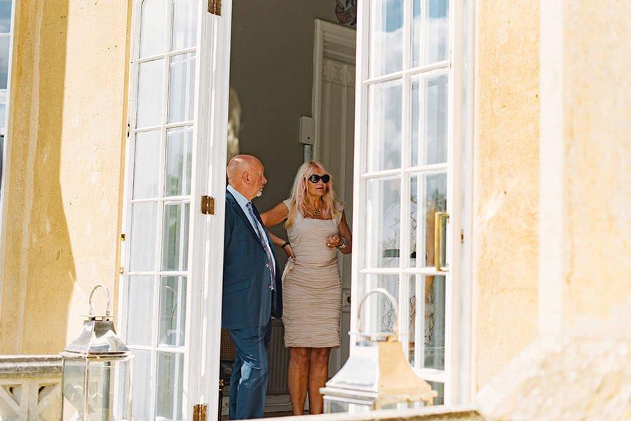wedding guests through an open door