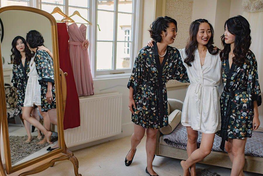 bridesmaids laughing wearing matching robes