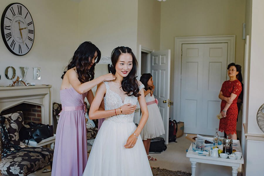 Chinese bride getting ready with her mother looking on