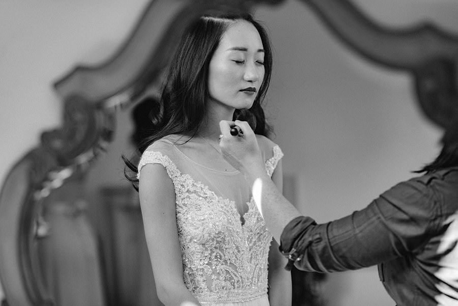 black and white photo of chinese bride having her makeup done in mirror