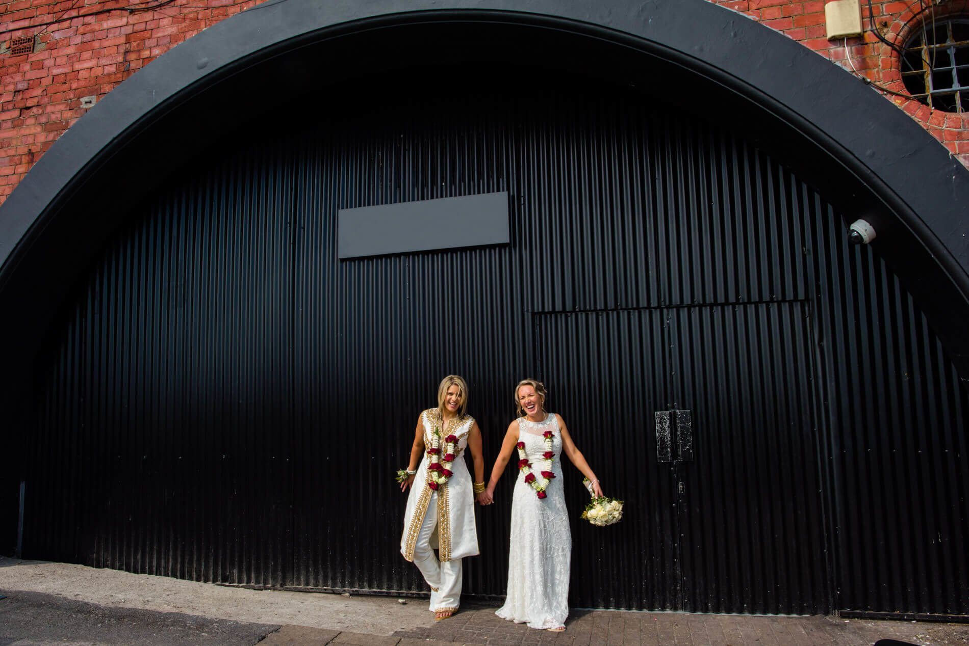 two brides laughing in front of black door
