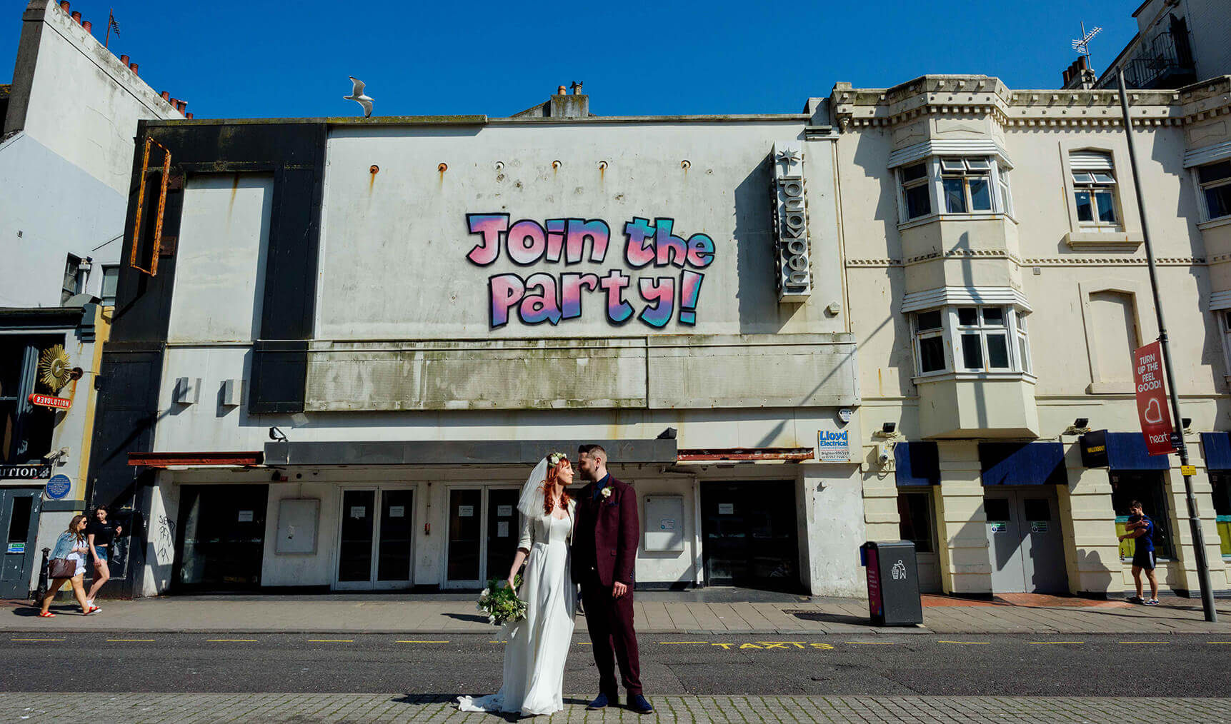 bride and groom on the street in front of a nightclub