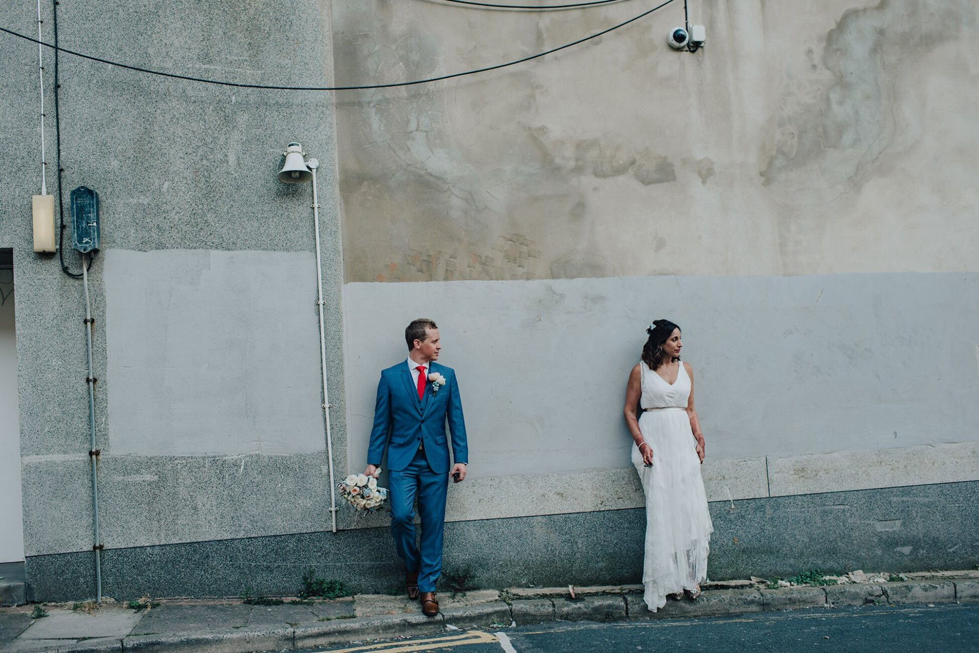 groom holding flowers and bride looking away in an urban setting in brighton