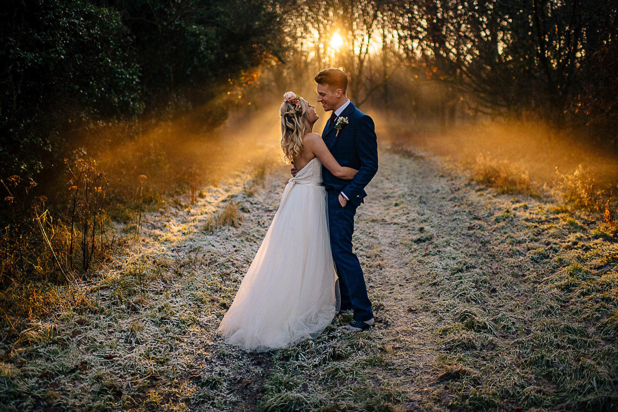 bride and groom in mazing winter light with frost on the grounds and sun setting behind them. golden hour wedding photography