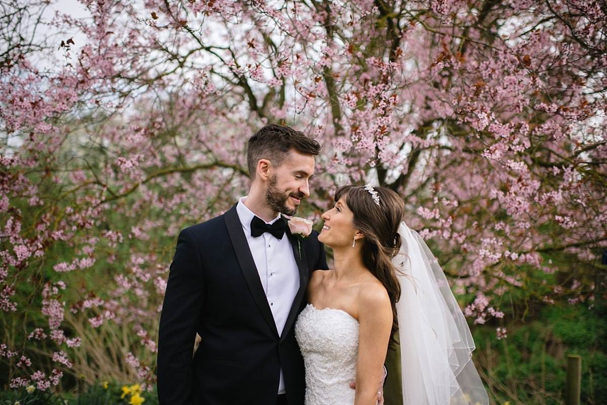 bride and groom in front of blossom