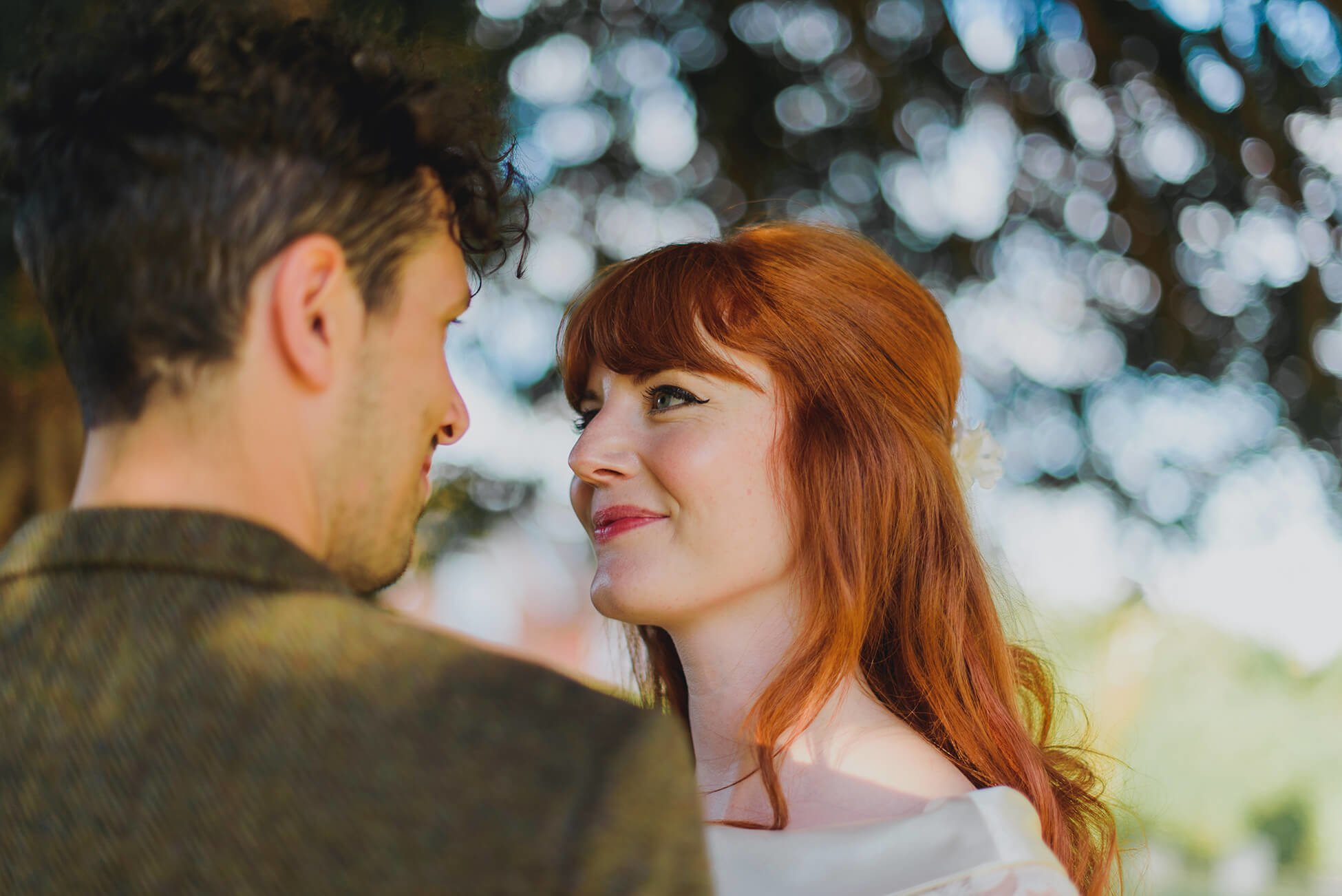 bride with red hair gazes at her groom