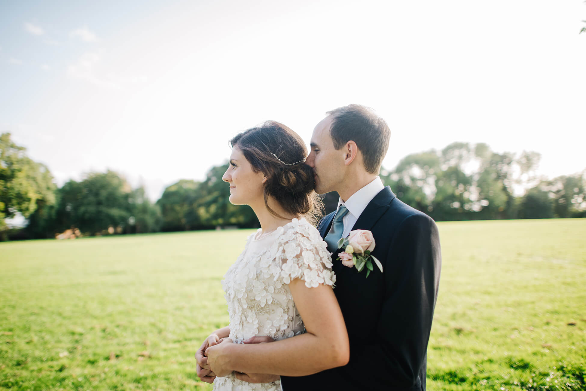 groom nuzzling brides hair enjoying the evening light sussex wedding photographer