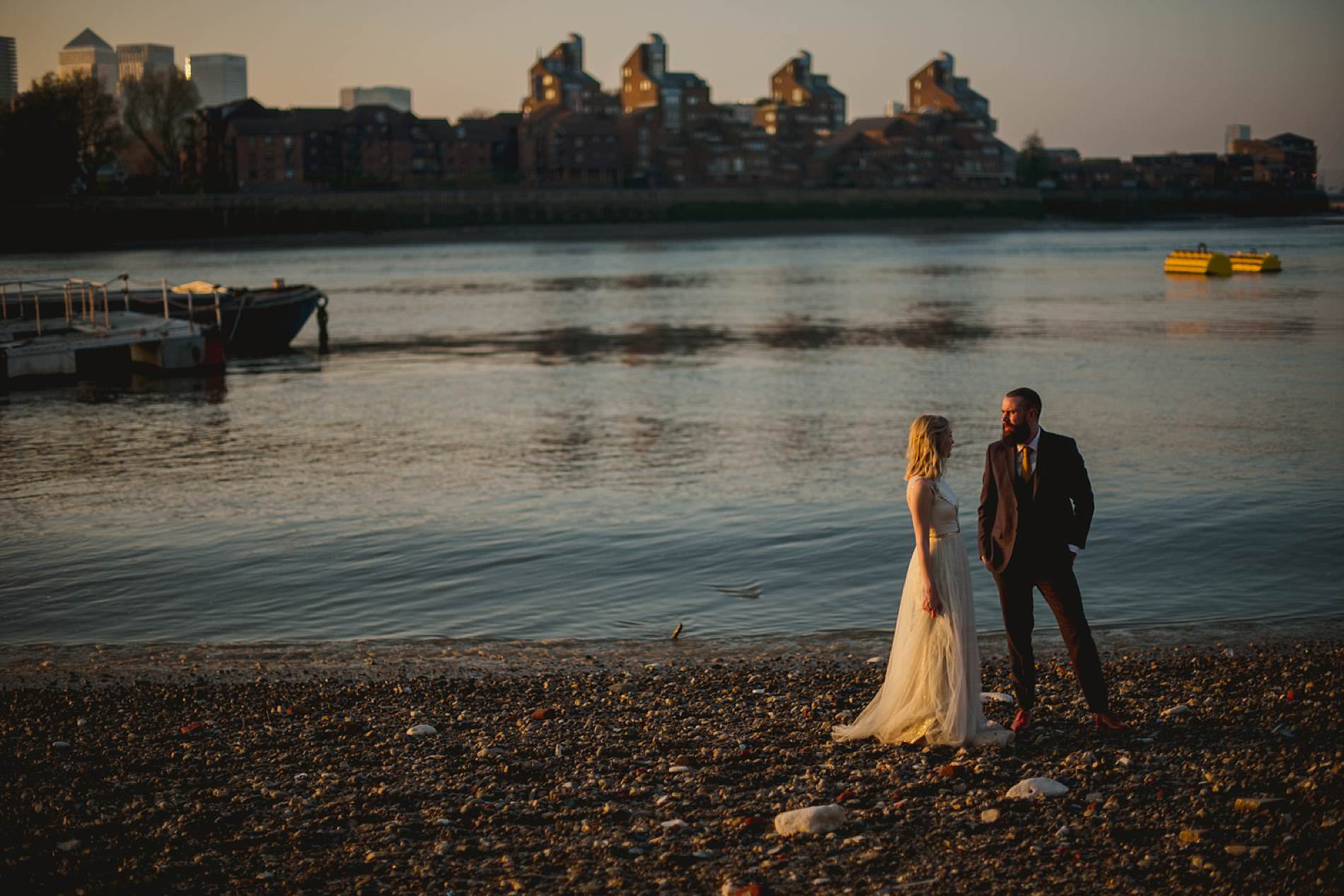 bride and groom by the river in london