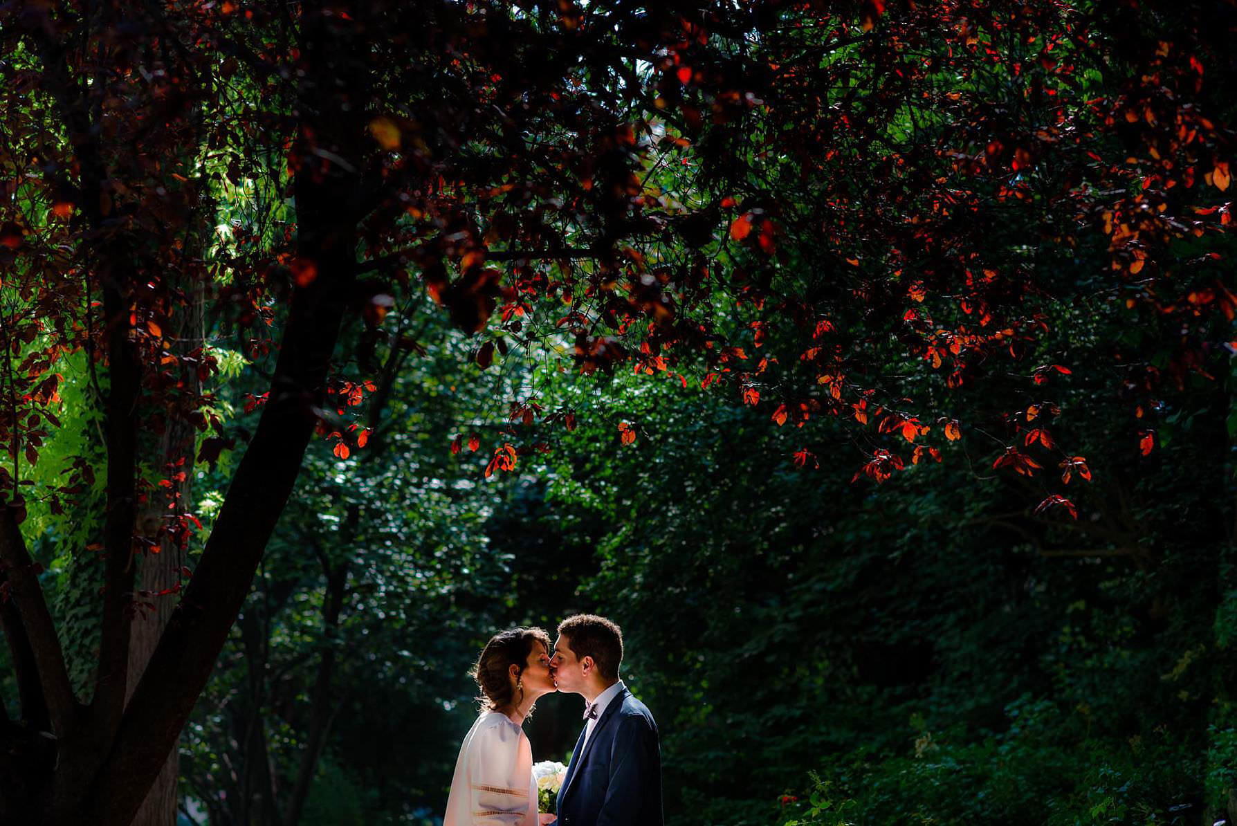 bride and groom kissing by cherry trees