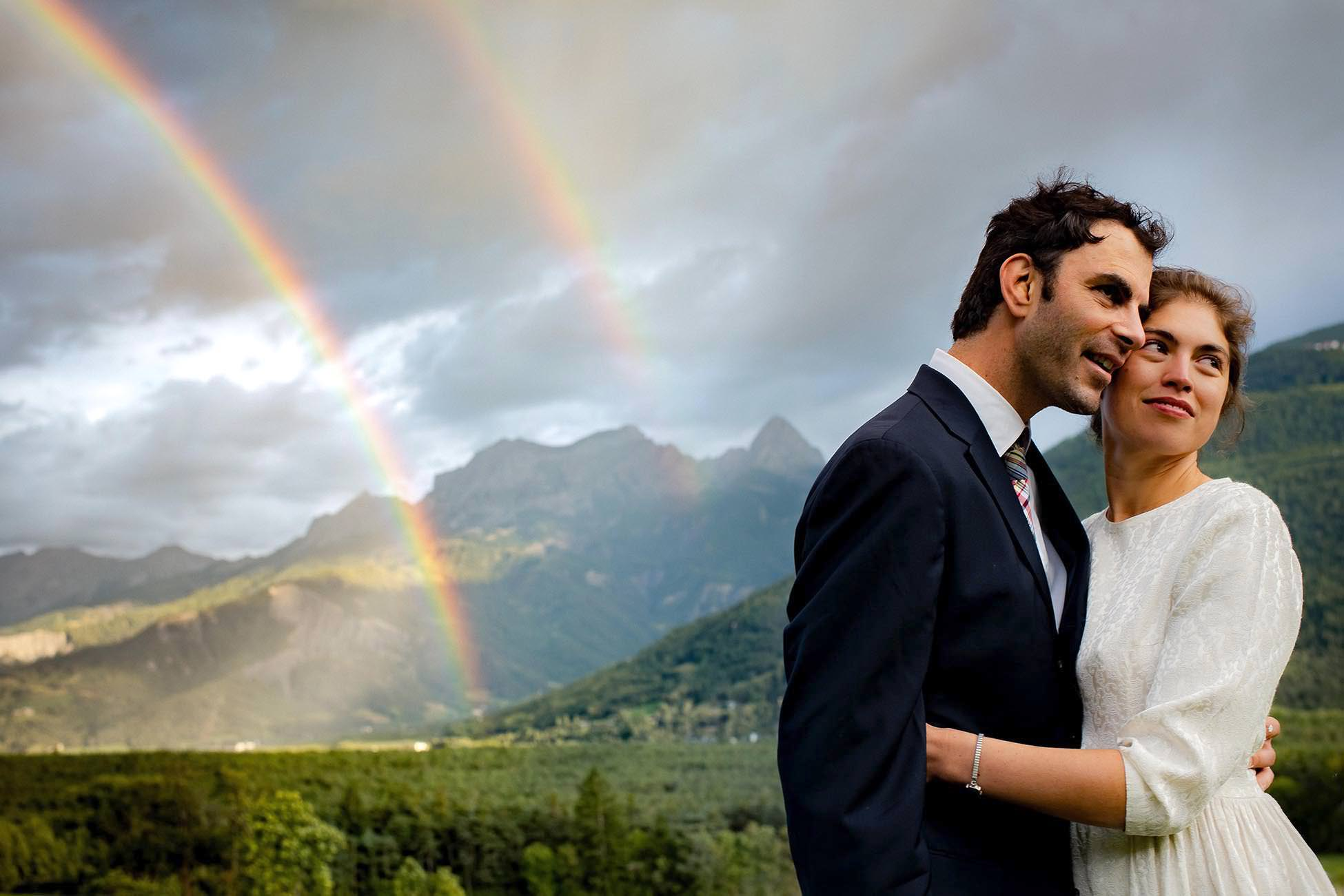 Bride and groom under a double rainbow in the french alps