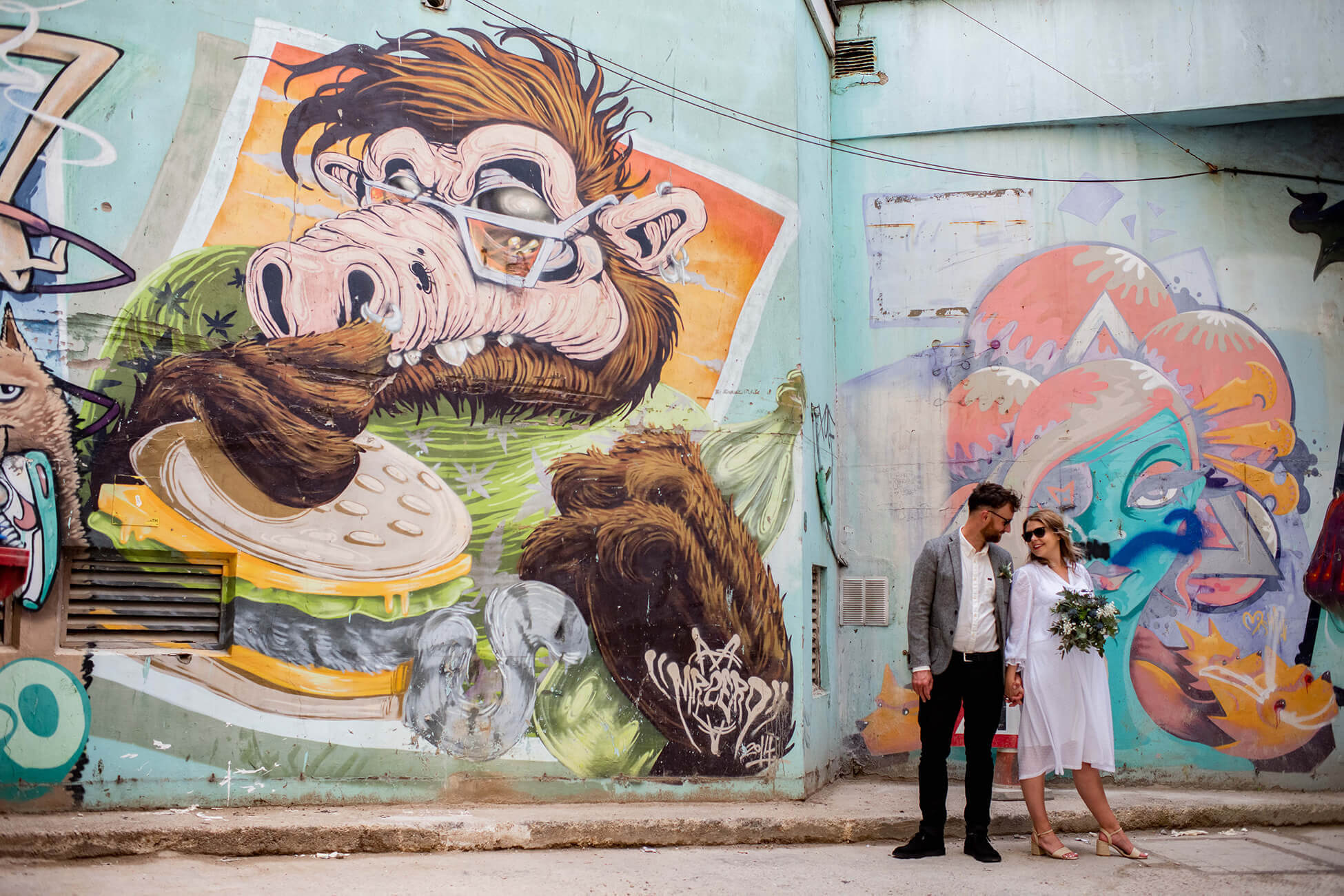 bride and groom in front of graffiti wall in brighton
