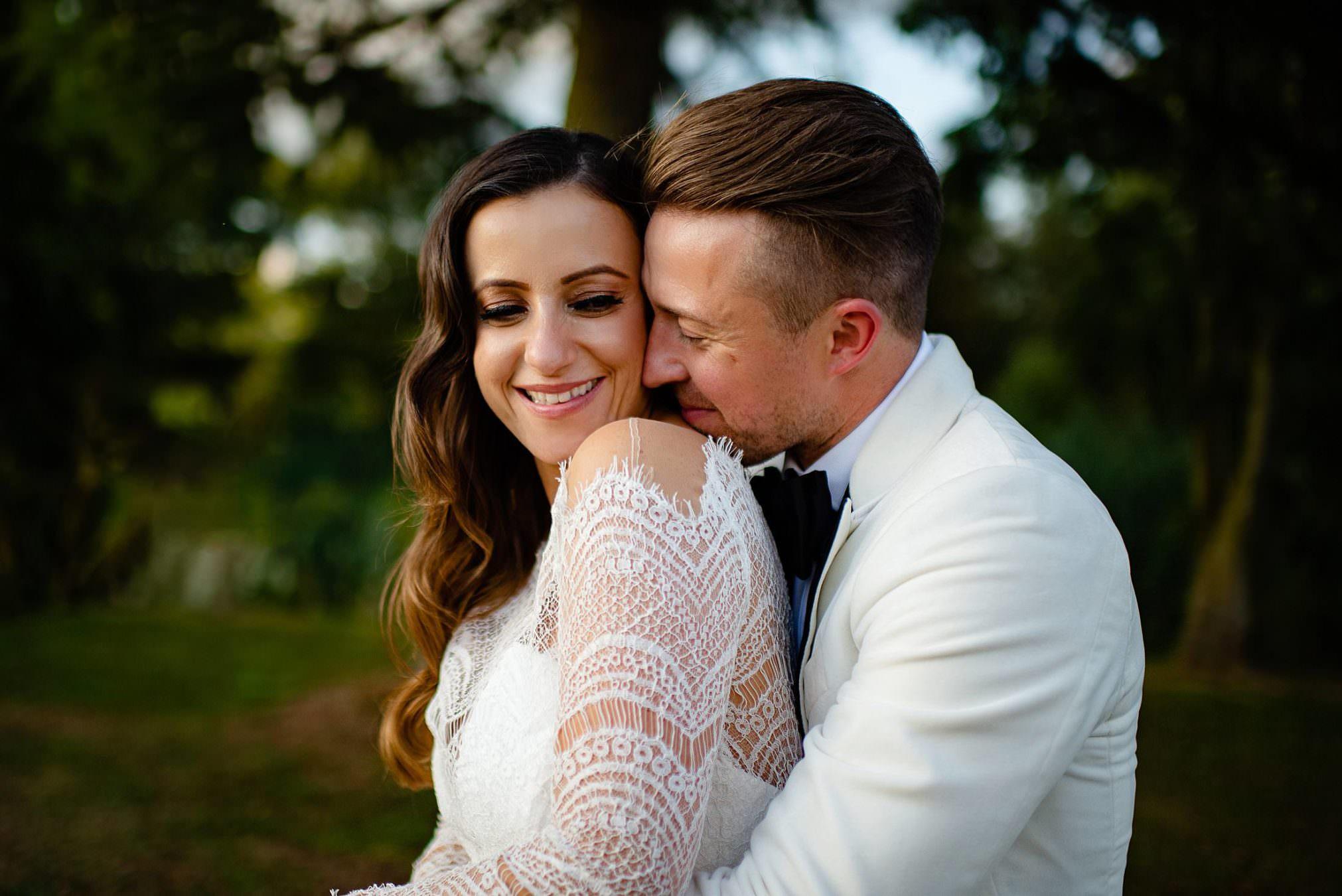 GRROM SNUGGLING INTO BRIDE